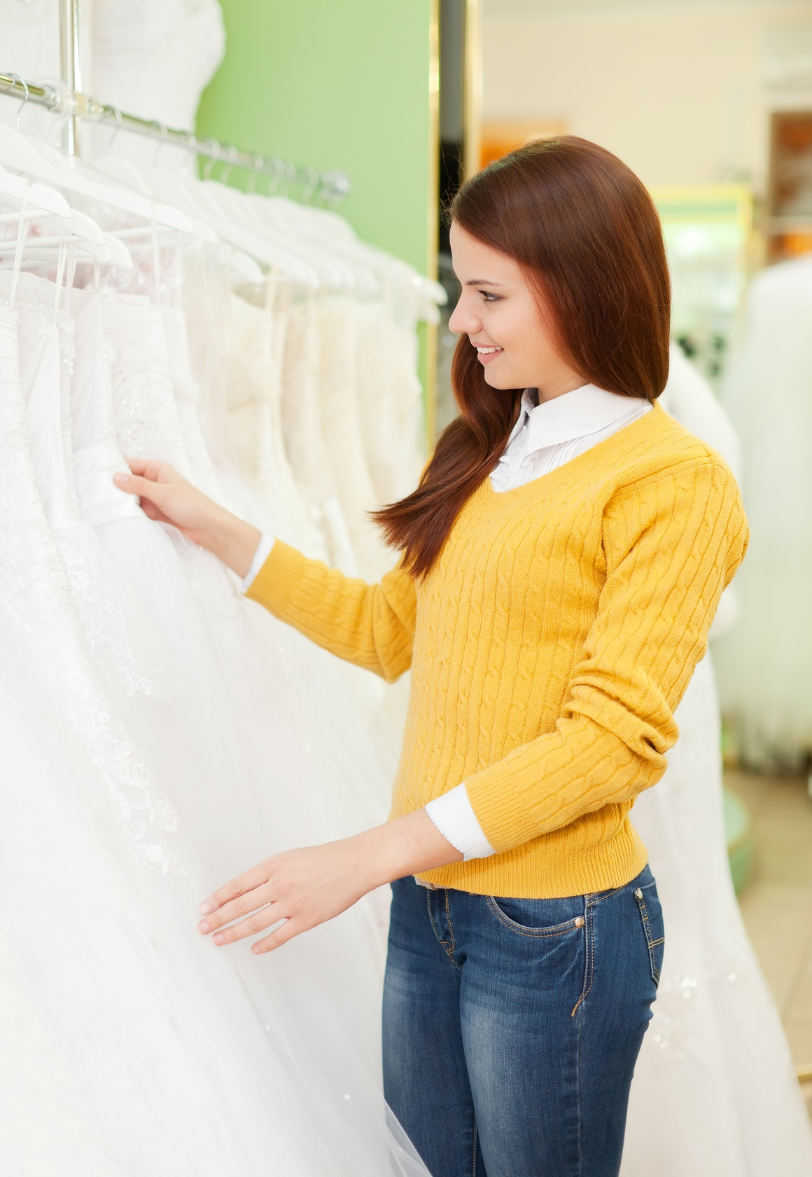Smiling pretty woman chooses white dress at shop of wedding fashion